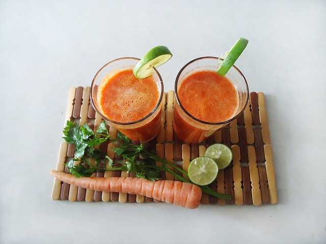 two glasses of carrot juice on cutting board