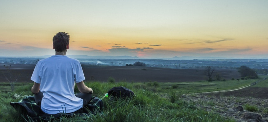 man meditating on hill in the morning