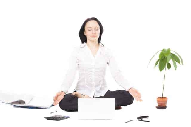 woman meditating on the floor of a white room with a laptop, money tree and other items around her