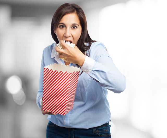 young pretty woman with brown hair and blue button up shirt stuffing popcorn into her mouth