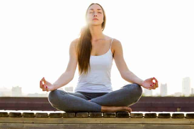 pretty young woman in white tank top with grey sweats meditating with fingers in circles and sun behind her