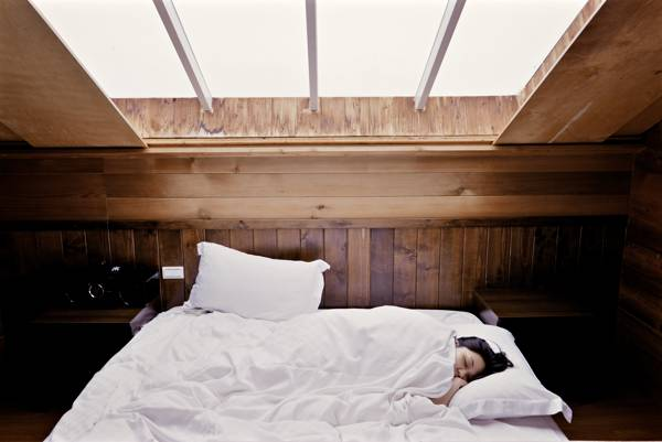 meditation and sleep - woman sleeping in bed with white sheets