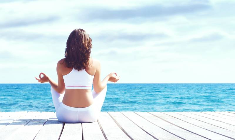 the importance of mediation - woman facing the ocean meditating