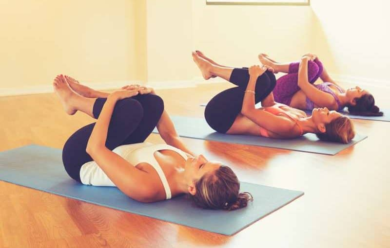 The health benefits of yoga - people stretching in yoga class