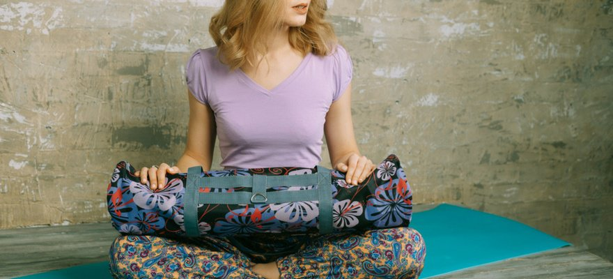 woman holding yoga mat bag