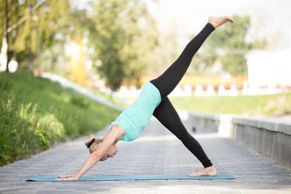 increasing the difficulty of downward facing dog in yoga - woman doing modified pose outside