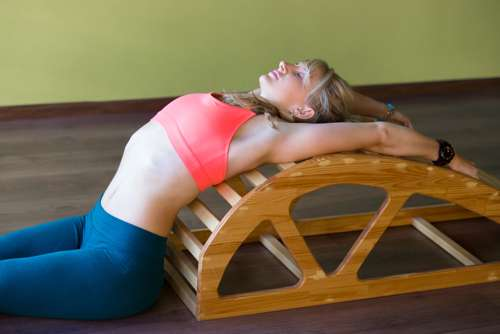 woman doing back bend over yoga prop - yoga for back pain