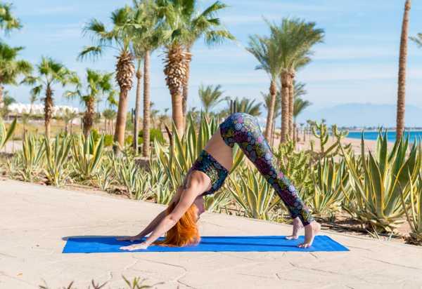 woman doing downward facing dog yoga outside