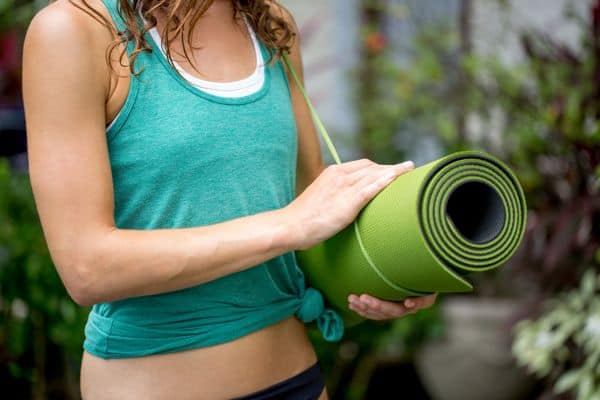 woman holding her yoga mat - how to choose a yoga mat