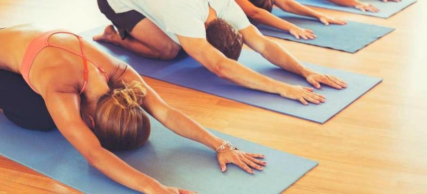 group doing hot yoga on blue yoga mats