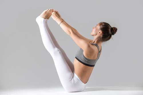 boat pose - yoga woman in white yoga pants