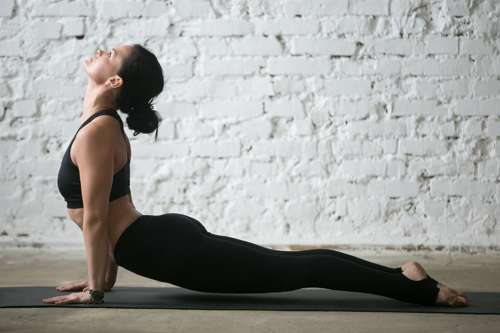 woman in black yoga outfit doing upward facing dog