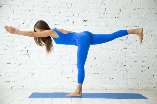woman in blue yoga outfit doing warrior 3 pose