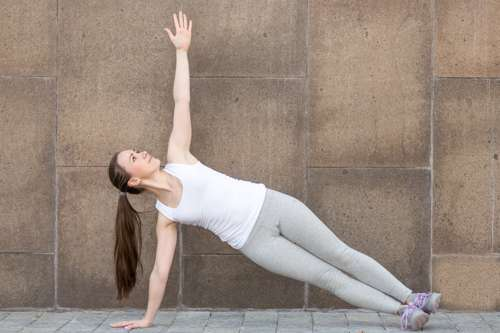woman in grey sweats and white shirt doing side plank pose