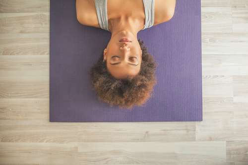 woman lying on yoga mat with eyes closed
