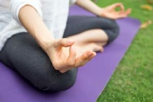 woman sitting on a purple yoga mat in zen position close up