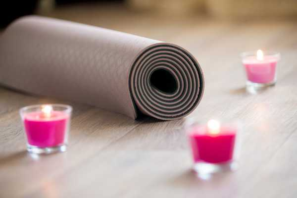 yoga mat with pink candles around it