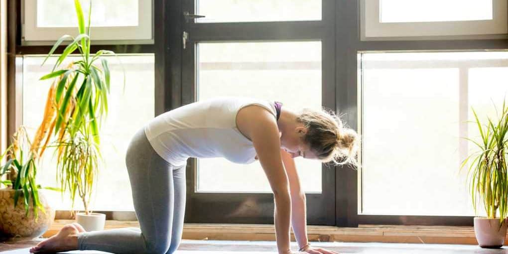 young woman kneeling on yoga mat - best mat for bad knees