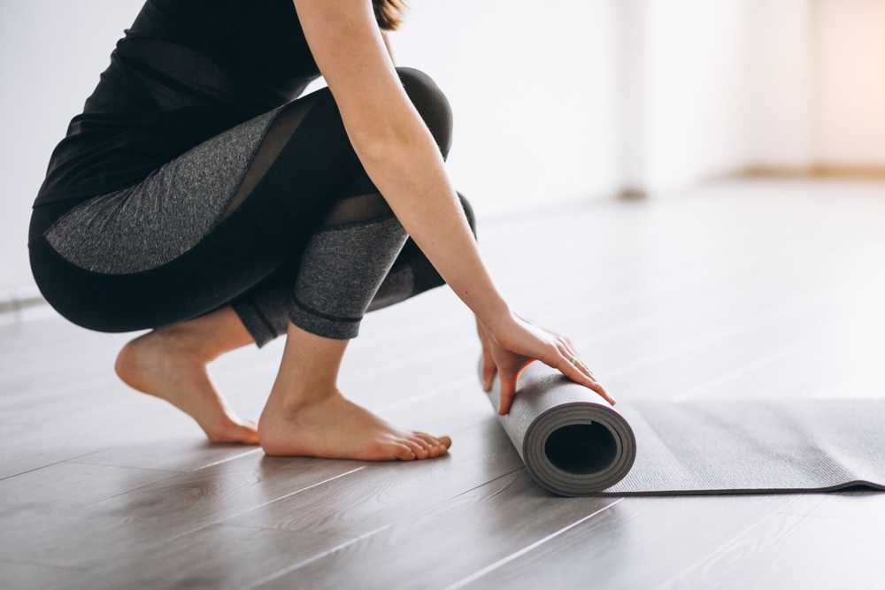 best yoga mats - woman rolling up black yoga mat