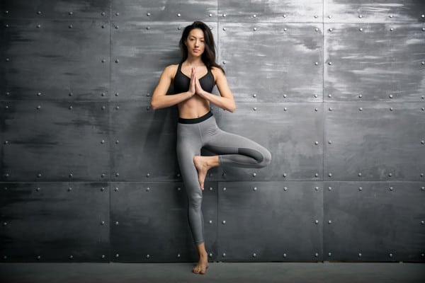 woman in yoga pose against wall