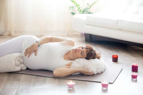 pregnant woman using pillow for corpse pose