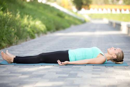 woman in teal shirt lying in corpse pose outside