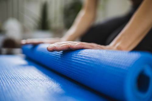 hands rolling up a yoga mat