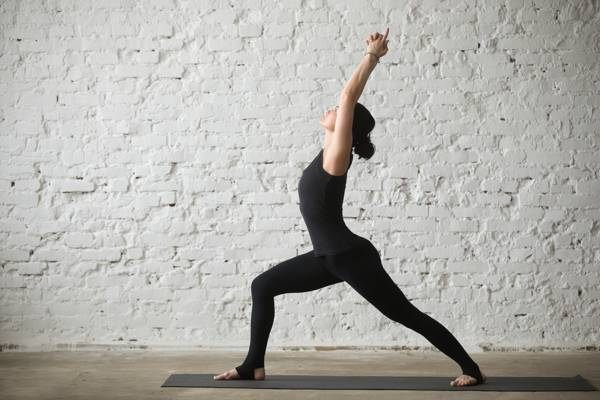woman doing warrior one pose