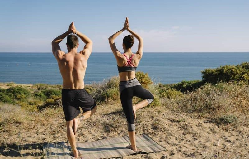 man and woman doing yoga on the beach - best yoga postures for men