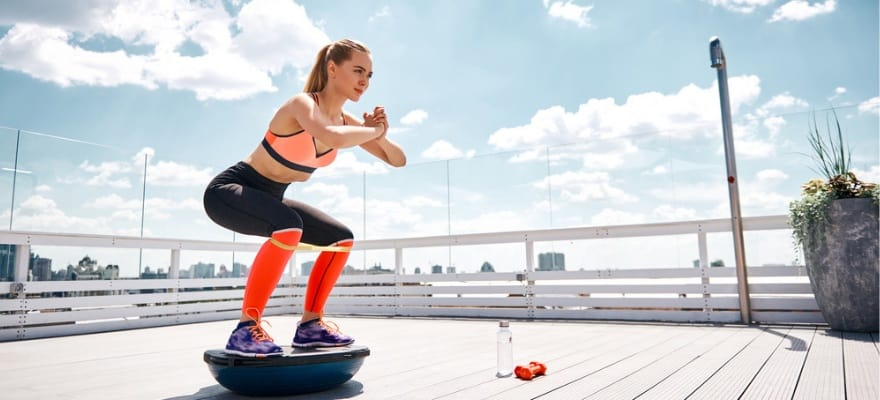 best cheap bosu ball - woman squatting on bosu ball