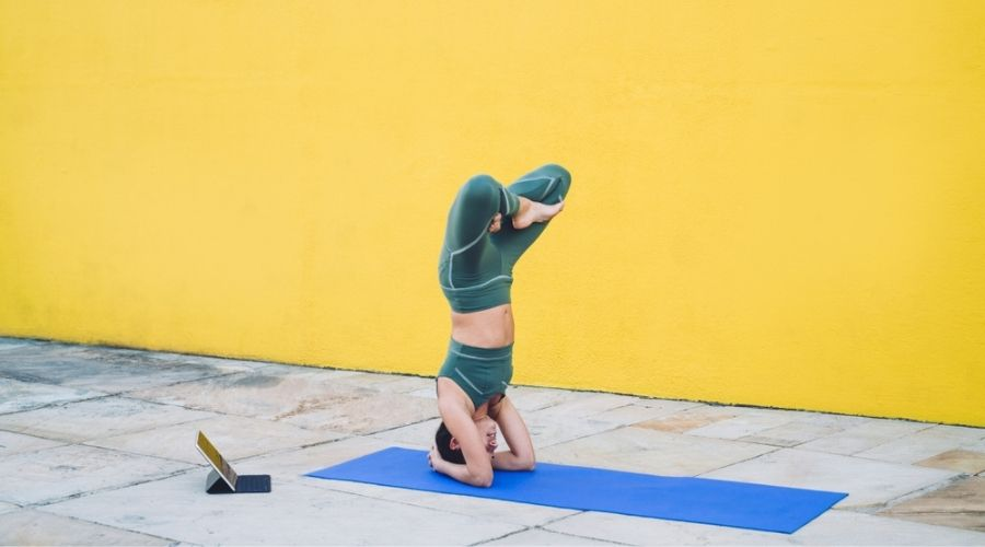 woman performing tripod headstand with lotus legs in front of large yellow wall