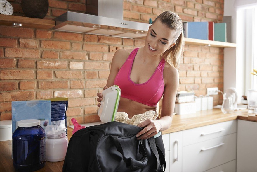 best gym bags for women - woman in pink shirt packing her workout bag