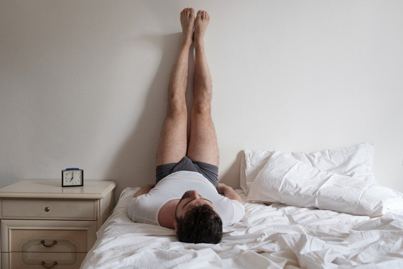 man performing legs up wall pose for relaxation in bed
