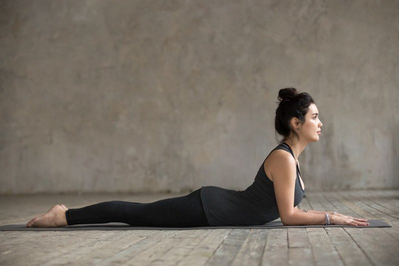 middle aged woman in black yoga outfit performing sphinx pose as yoga for relaxation