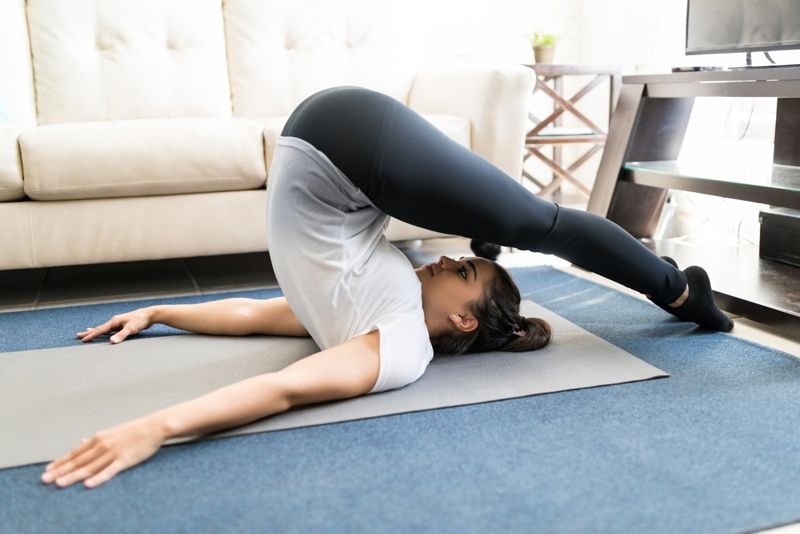 woman doing yoga with yoga mat on rug in house