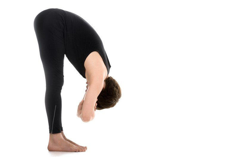 woman in black outfit doing yoga forward bend for relaxation