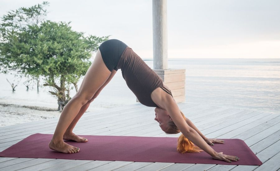 woman performing downward dog on yoga mat