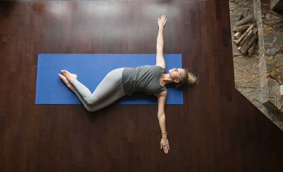 woman performing knees together supine twist