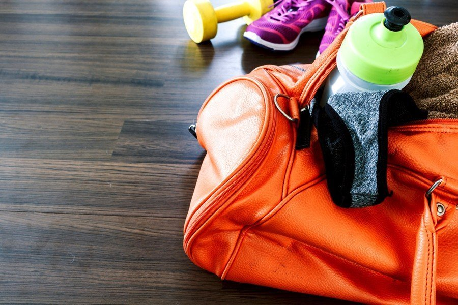 womens gym bag on the floor with stuff in it - best gym bags for women