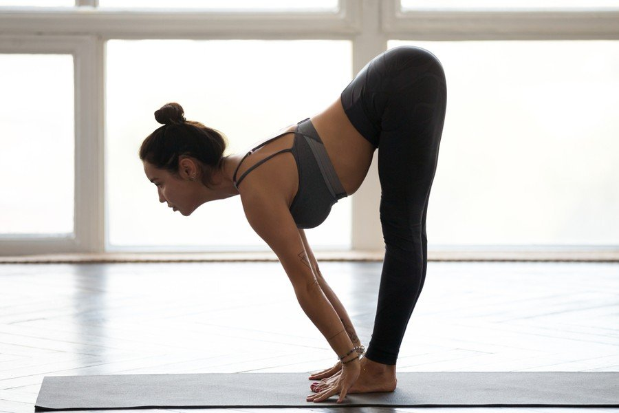 Standing forward bend yoga pose - young woman performing the pose