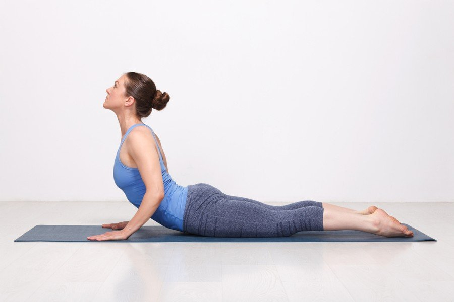 cobra pose - woman in blue yoga outfit performing the pose