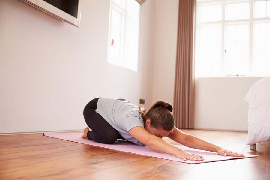 how to do to childs pose instructions - woman doing yoga in livingroom