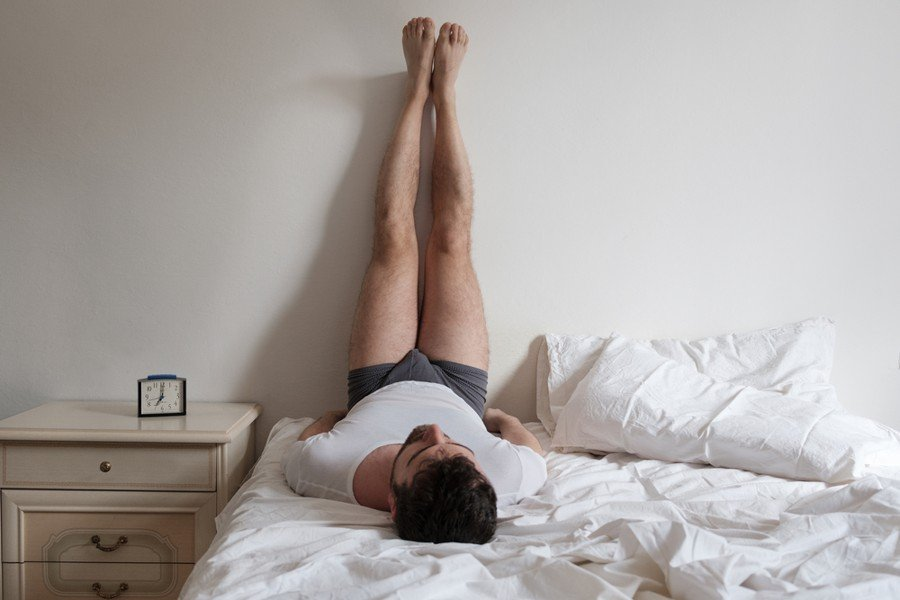 man doing legs up the wall pose in bed
