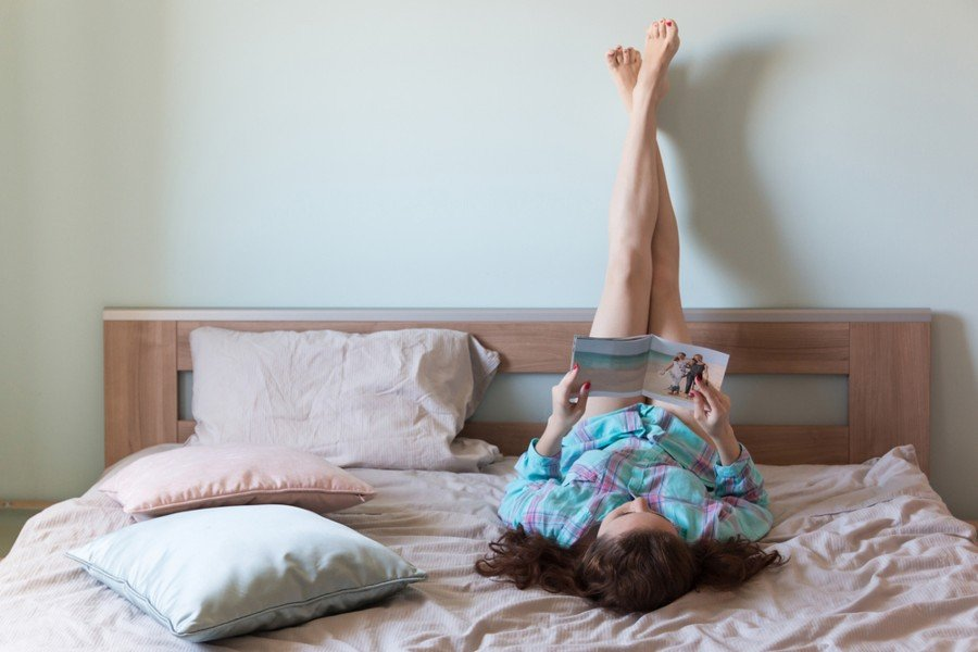 woman doing legs up the wall pose while reading in bed