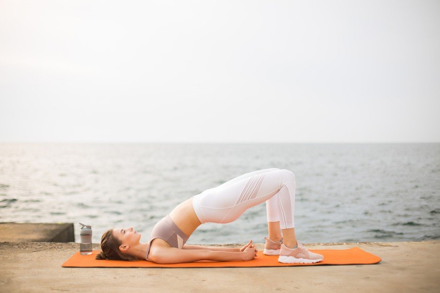 woman doing the bridge pose yoga at the beach