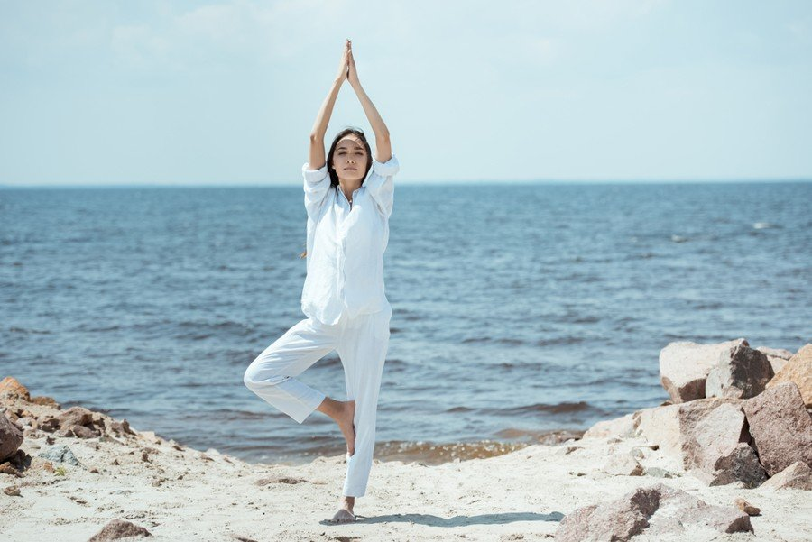 woman in all white doing a modified tree pose at the beach