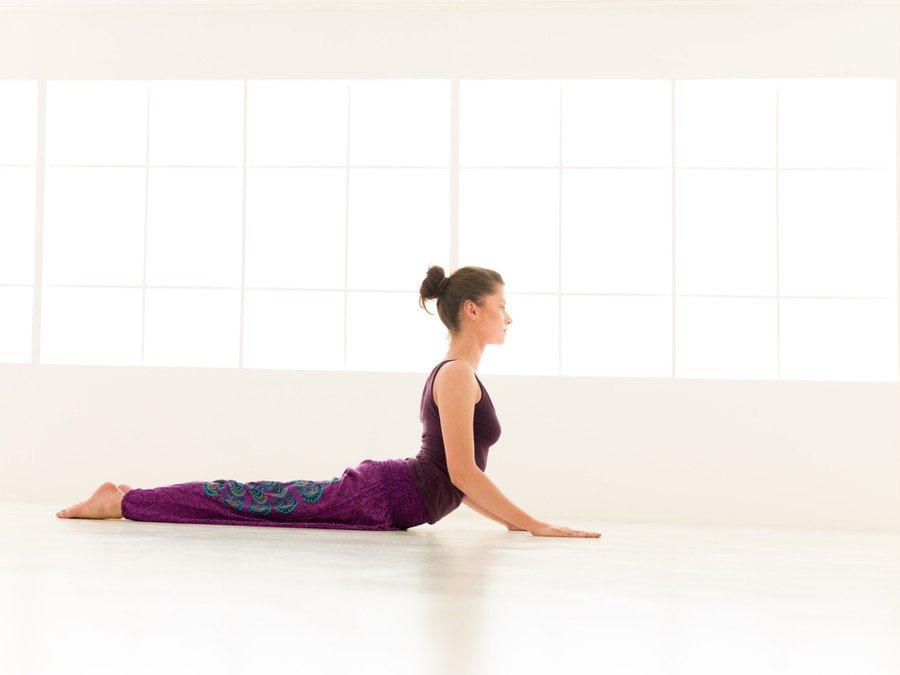 woman performing cobra pose in yoga room