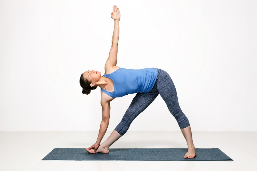 Woman doing extended triangle pose on yoga mat in studio