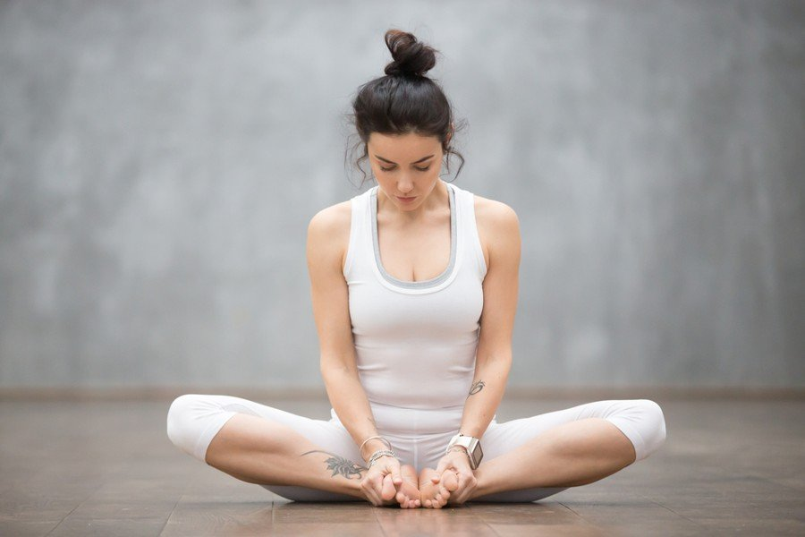 Woman performing bound angle yoga pose