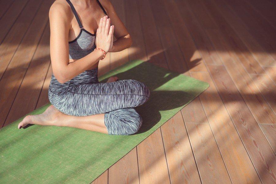 choosing a yoga mat - woman practicing yoga on green yoga mat